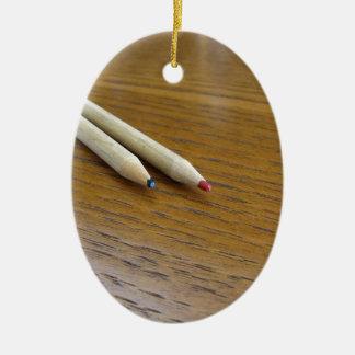 Ornement Ovale En Céramique Deux crayons colorés utilisés sur la table en bois