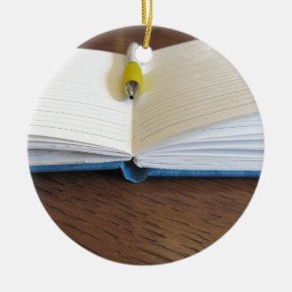 Ornement Rond En Céramique Carnet rayé par blanc ouvert avec le stylo