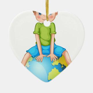 Petit garçon s'asseyant sur la planète bleue ornement cœur en céramique