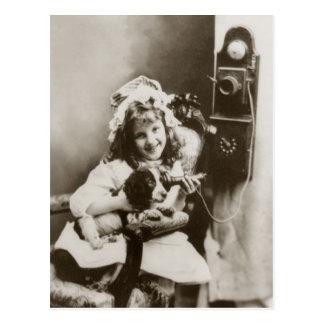 Petite fille et chiot jouant avec le téléphone carte postale