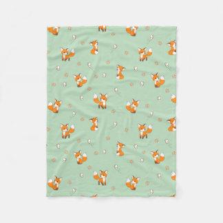 Petits renards mignons sur le vert couverture polaire