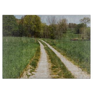 Planche À Découper Chemin rural dans le paysage vert de ressort