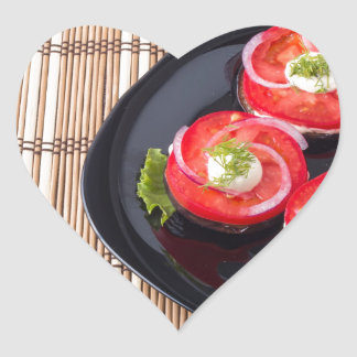 Plat noir avec les tomates et la laitue coupées en sticker cœur