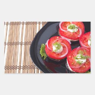 Plat noir avec les tomates et la laitue coupées en sticker rectangulaire