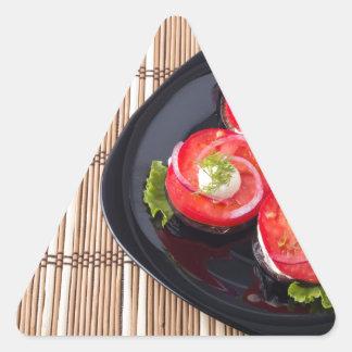 Plat noir avec les tomates et la laitue coupées en sticker triangulaire