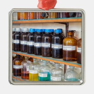 Rangées des produits chimiques liquides dans des ornement carré argenté