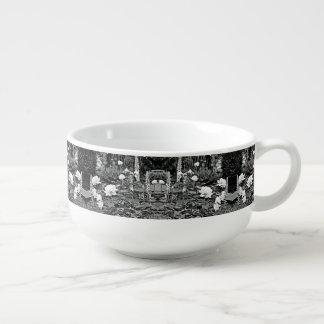 Rose blanc dans la tasse noire de soupe à jardin