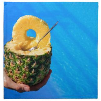 Serviettes En Tissus Main tenant l'ananas frais au-dessus de la piscine