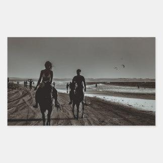 Sticker Rectangulaire Jeunes chevaux d'équitation de couples à la plage