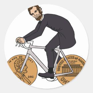 Sticker Rond Abraham Lincoln sur un vélo avec le penny roule la