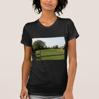 T-shirt Pelouse verte avec la barrière et les arbres en