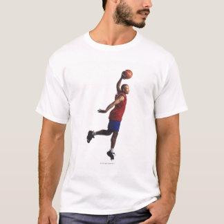 T-shirt un jeune joueur de basket de mâle adulte vole