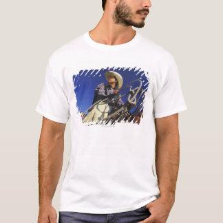 T-shirt Vue d'angle faible d'un cowboy montant un cheval,