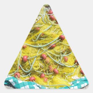 Tas de filet jaune sur la terre en mer sticker triangulaire