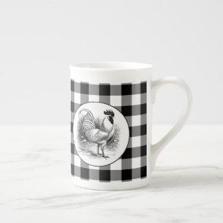 Tasse blanche noire de porcelaine de coq de pays