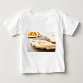 Tranches de fromage et de pain sur un plan t-shirt pour bébé