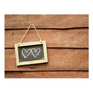 Twee die harten op klein bord op tuin worden briefkaart