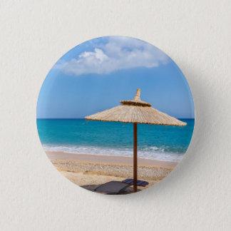 Un parapluie et chaises longues de plage badge rond 5 cm