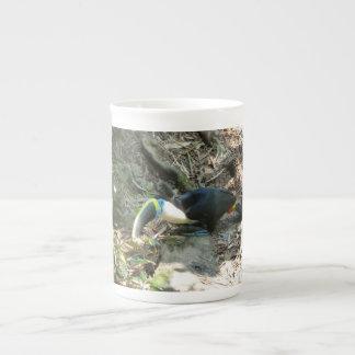 Un toucan est perché sur des racines d'arbre sur mug