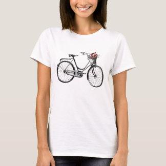 Vélo vintage avec des T-shirts de panier de fleur