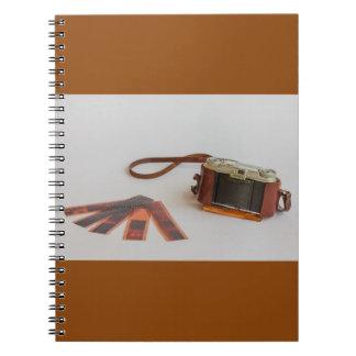 vieil appareil-photo avec le négatif sur   le carnets à spirale