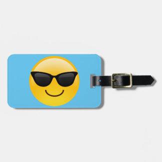 Visage de sourire avec des lunettes de soleil étiquettes bagages