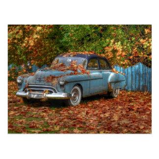 Voiture ancienne dans le feuille d'automne carte postale