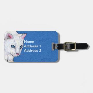 Yeux bleu-clair lumineux de chat assez blanc étiquette à bagage